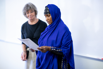 Adult ESL learner reading a paper with volunteer standing close beside her