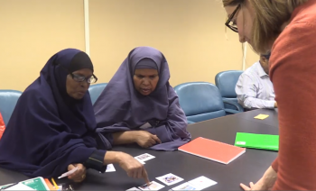 Adult ESL teacher talking to two learners sitting at a table
