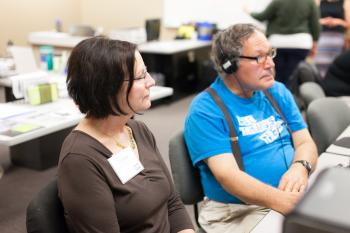 Adult learner wearing headphones looking at a computer with a volunteer looking on